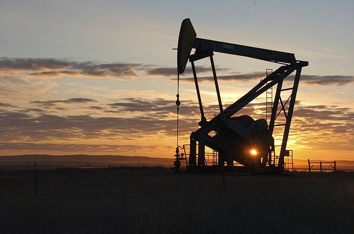 This Nov. 6, 2013 file photo shows a Whiting Petroleum Co. pump jack pulls crude oil from the Bakken region of the Northern Plains near Bainville, Mont. As the Trump administration rolls back environmental and safety rules for the U.S. energy sector, government projections show billions of dollars in savings reaped by companies will come at a steep cost: increased premature deaths and illnesses from air pollution, a jump in climate-warming emissions and more derailments of trains carrying explosive fuels. (Matthew Brown/AP, file)