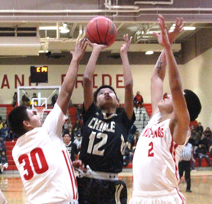 Chinle Wildcat freshmen Kylen Yazzie splits Monument Valley Mustang defenders Latrell Maloney and Hunter Nez for a two point basket attempt, during a 3A north basketball game at the Nash Center, in Kayenta, Arizona.  (Anton Wero/NHO)