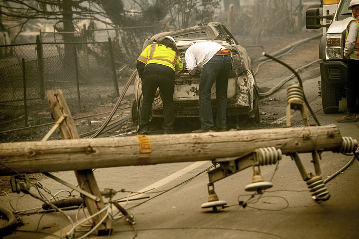 In this Nov. 10, 2018 file photo, with a downed power utility pole in the foreground, Eric England, right, searches through a friend's vehicle after the wildfire burned through Paradise, Calif. Pacific Gas & Electric Corp. is expected to file for bankruptcy protection Tuesday, Jan. 29, 2019. (AP Photo/Noah Berger, File)