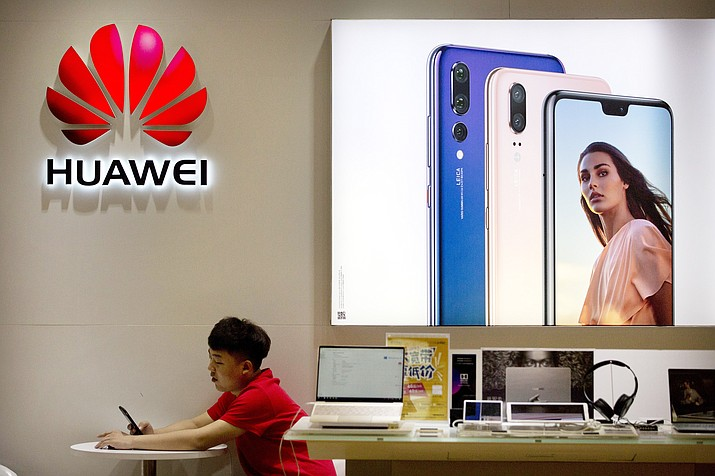 In this July 4, 2018, file photo, a sales clerk looks at his smartphone in a Huawei store at a shopping mall in Beijing. China has called on the United States to 'stop the unreasonable crackdown' on Huawei following the tech giant's indictment on charges of stealing technology, violating trade sanctions and lying to banks. (AP Photo/Mark Schiefelbein, File)