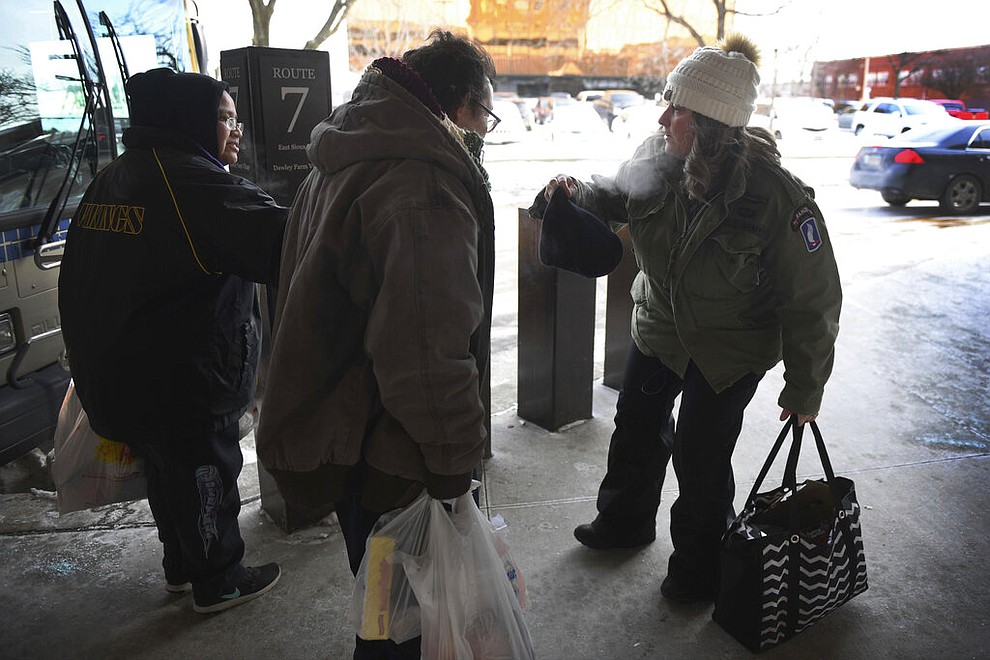 Amy Lawrence, right, helps someone wear a hat as she walks around the downtown bus stop terminal, handing out hand warmers to passengers in Sioux Falls, S.D., Tuesday, Jan. 29, 2019. Temperatures in the Dakotas and Minnesota dropped on Tuesday to as low as minus 27 (negative 33 degrees Celsius) with wind chills as cold as minus 59 (negative 51 degrees Celsius). (Briana Sanchez/The Argus Leader via AP)