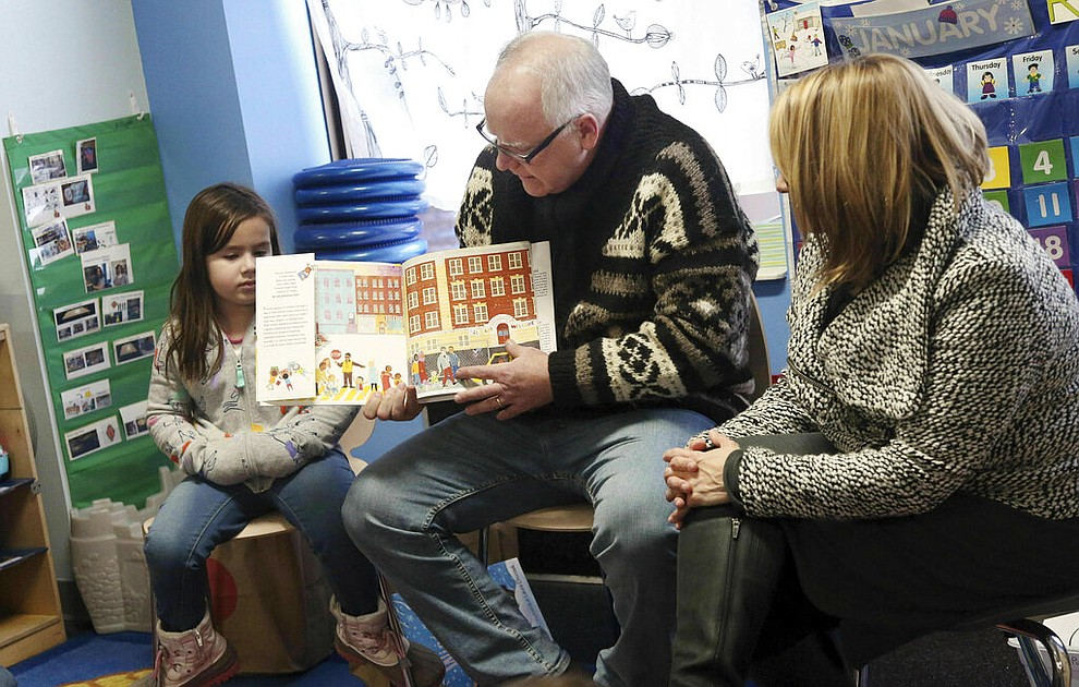 Gov. Tim Walz, top, reads a book to children at People Helping People, a shelter for families experiencing homelessness amid extreme cold weather conditions in Minnesota Tuesday, Jan. 29, 2019, in Minneapolis, accompanied by Lt. Gov. Peggy Flanagan, right. (AP Photo/Jim Mone)
