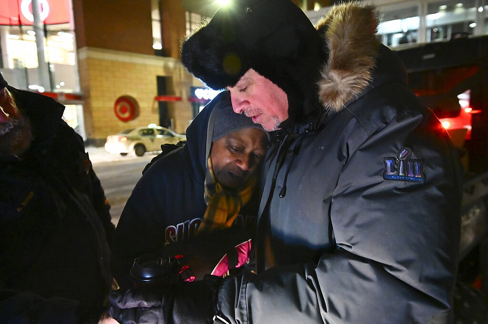 Pastor John Steger, with Grace In The City church, embraces Jearline Cyrus, a homeless woman, in downtown Minneapolis, Tuesday, Jan. 29, 2019, while delivering cold-weather gear, hot chocolate and food with Minneapolis Police Sgt. Grant Snyder. Snyder will be hitting the streets Tuesday and Wednesday night during the height of the big chill to check on the welfare of homeless people who haven't made it into a shelter. (Aaron Lavinsky/Star Tribune via AP)