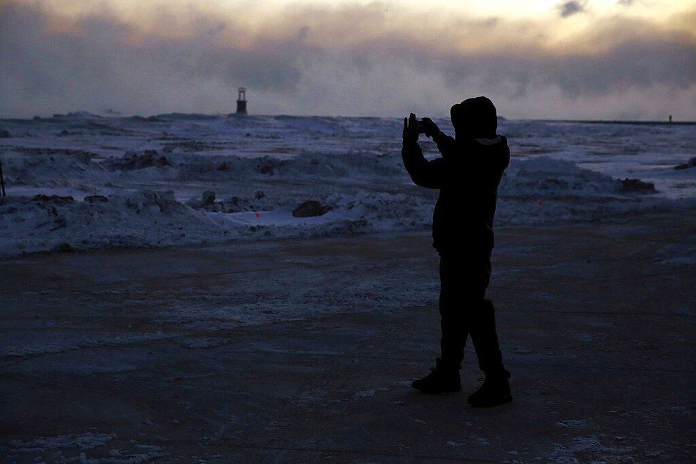 A man takes pictures as ice forms along the shore of Lake Michigan, Wednesday, Jan. 30, 2019, in Chicago. A deadly arctic deep freeze enveloped the Midwest with record-breaking temperatures on Wednesday, triggering widespread closures of schools and businesses, and prompting the U.S. Postal Service to take the rare step of suspending mail delivery to a wide swath of the region. (AP Photo/Kiichiro Sato)