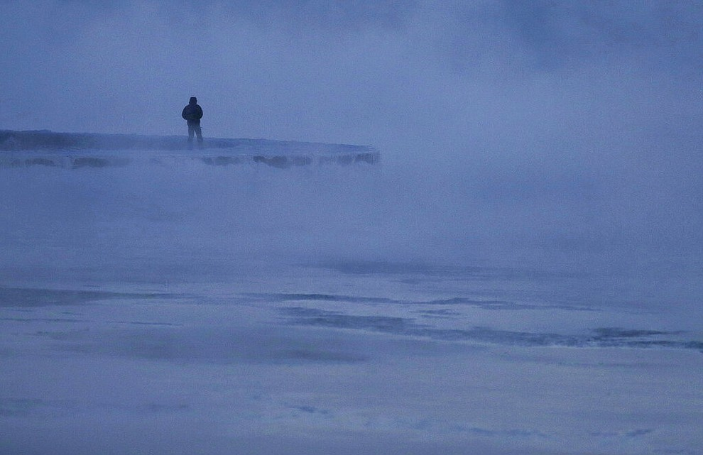 A man walks along the shore of Lake Michigan, Wednesday, Jan. 30, 2019, in Chicago. A deadly arctic deep freeze enveloped the Midwest with record-breaking temperatures on Wednesday, triggering widespread closures of schools and businesses, and prompting the U.S. Postal Service to take the rare step of suspending mail delivery to a wide swath of the region. (AP Photo/Kiichiro Sato)