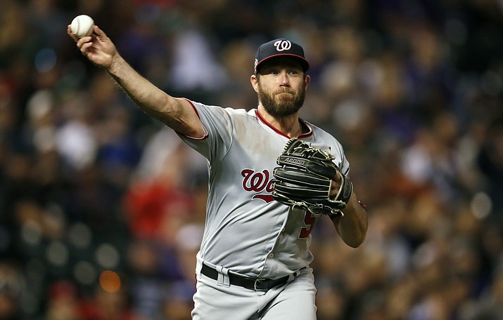 In this  Saturday, Sept. 29, 2018 file photo, Washington Nationals relief pitcher Greg Holland throws to first base to put out Colorado Rockies' DJ LeMahieu in the eighth inning of a baseball game in Denver. Two people familiar with the negotiations say reliever Greg Holland and the Arizona Diamondbacks have agreed to a $3.25 million, one-year contract. The people spoke to The Associated Press on condition of anonymity Wednesday, Jan. 30, 2019 because the agreement had not been announced. (David Zalubowski/AP, File)