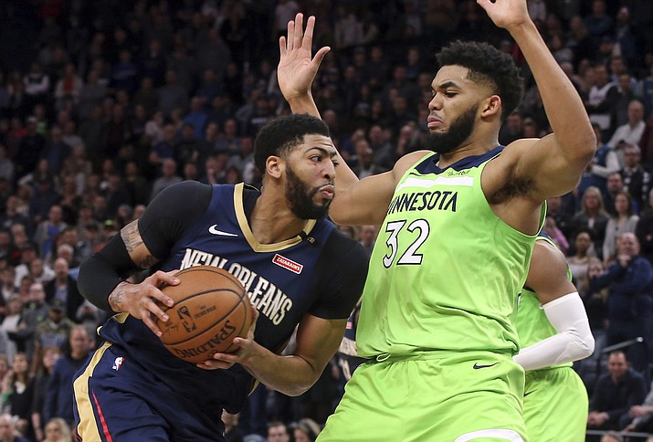 New Orleans Pelicans' Anthony Davis, left, drives as Minnesota Timberwolves' Karl-Anthony Towns defends in the second half of an NBA basketball game Saturday, Jan. 12, 2019, in Minneapolis. (Jim Mone/AP)