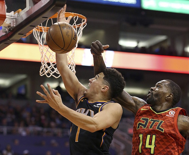 Phoenix Suns guard Devin Booker (1) has his shot blocked by Atlanta Hawks center Dewayne Dedmon (14) during the first half of an NBA basketball game Saturday, Feb. 2, 2019, in Phoenix. (Ross D. Franklin/AP)