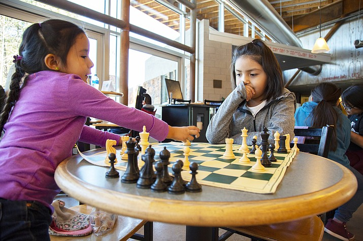 Hailey Willie, 7, (right), watches Kassidy Holgate, 5, both from Navajo Mountain, prepare to make a move during a practice session before the second round of the Fifth annual All-Girls Chess Tournament at Coconino Community College Jan. 26. (Photo/Coconino Community College)