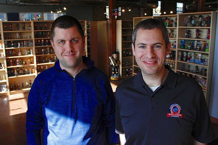 In this Jan. 8, 2019 photo, National Bobblehead Hall of Fame and Museum co-founders Brad Novak, left, and Phil Sklar, who started collecting figures 16 years ago, pose for a photo near the entrance of the National Bobblehead Hall of Fame and Museum in Milwaukee. The new museum is displaying more than 6,500 figures of athletes, mascots, celebrities, animals, cartoon characters, politicians and more. (AP Photo/Carrie Antlfinger)