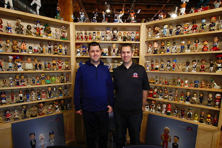In this Jan. 8, 2019 photo, National Bobblehead Hall of Fame and Museum founders Brad Novak, left, and Phil Sklar, stand near the museum entrance at the National Bobblehead Hall of Fame and Museum in Milwaukee. The new museum may well hold the largest collection of bobbleheads anyone has ever seen, displaying more than 6,500 figures of athletes, mascots, celebrities, animals, cartoon characters, politicians and more. (AP Photo/Carrie Antlfinger)