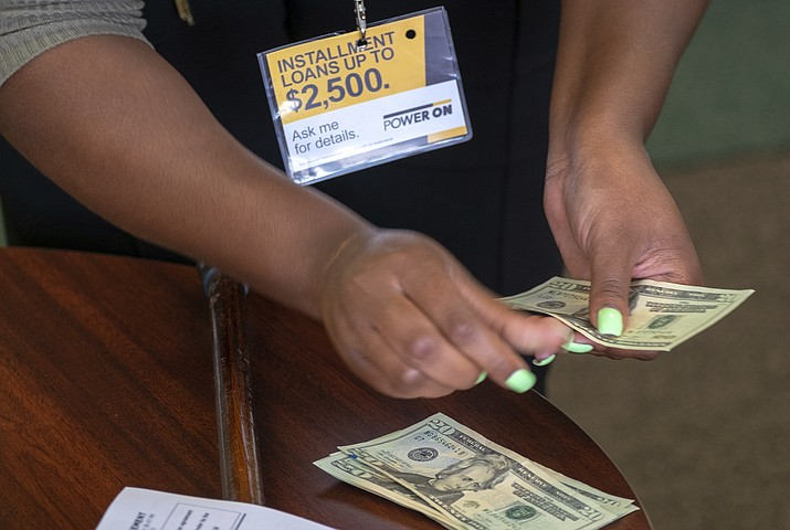 A manager of a financial services store in Ballwin, Mo., counts cash being paid to a client as part of a loan. The nation's federal financial watchdog has announced its plans to roll back most of its consumer protections governing the payday lending industry. (Sid Hastings/AP, File)