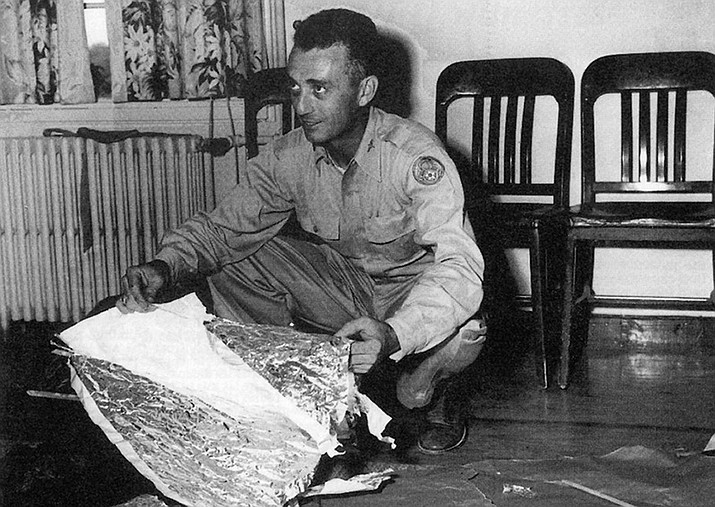 "Roswell Army Air Field Intelligence Officer Jesse Marcel, Sr. inspects fragments of an object that crashed at a ranch near Roswell, New Mexico in 1947. Following wide initial interest in the crashed ""flying disc,"" the U.S. military stated that it was merely a conventional weather balloon. (United States Army file photo)"