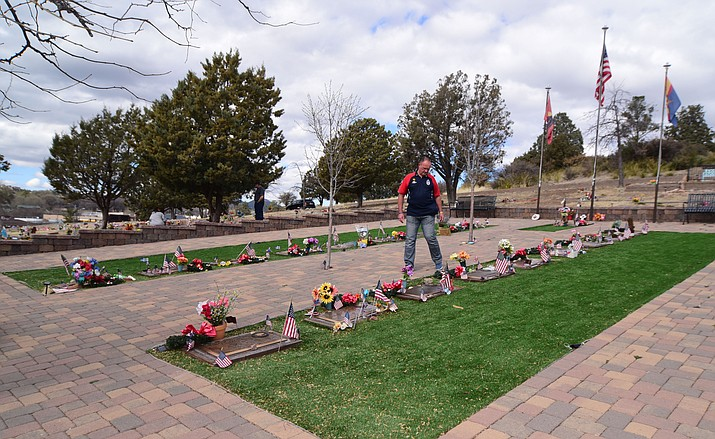Waz Taylor, from Sheffield, England, places a piece of granite from Leicester, England, on each Granite Mountain Hotshot grave at the Arizona Pioneers Cemetery Friday, Feb. 1, 2019. (Les Stukenberg/Courier)