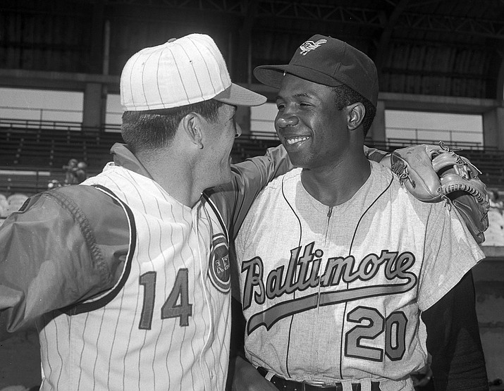 In this April 1, 1966, file photo, Cincinnati Reds' Pete Rose, left, greets Baltimore Orioles' Frank Robinson before a spring training baseball game, in Tampa, Fla. Hall of Famer Frank Robinson, the first black manager in Major League Baseball and the only player to win the MVP award in both leagues, has died. He was 83. Robinson had been in hospice care at his home in Bel Air. MLB confirmed his death Thursday, Feb. 7, 2019. (AP Photo/Paul Shane, File)