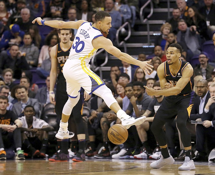 Phoenix Suns guard Elie Okobo, right, passes underneath a jumping Golden State Warriors guard Stephen Curry (30) during the first half of an NBA basketball game Friday, Feb. 8, 2019, in Phoenix. (Ross D. Franklin/AP)