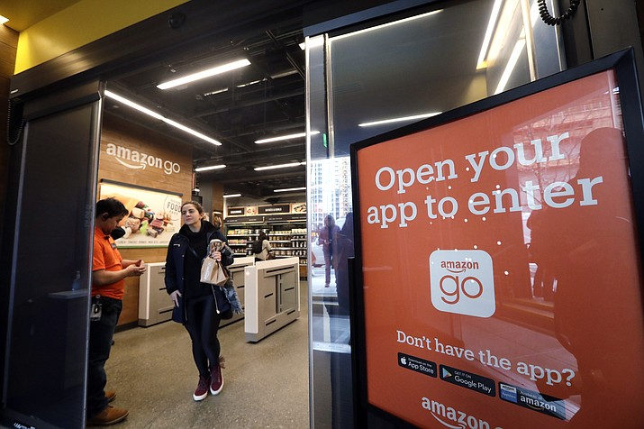A shopper leaves an Amazon Go store in Seattle. Get ready to say good riddance to the checkout line. A year after Amazon opened its first cashier-less store, startups and retailers are racing to get similar technology in other stores throughout the world, letting shoppers buy groceries without waiting in line. (Elaine Thompson/AP, File)