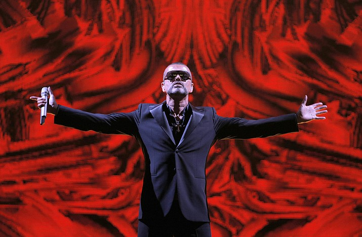 """British singer George Michael performs at a Sept. 9, 2012 concert to raise money for the AIDS charity Sidaction, during the Symphonica tour at Palais Garnier Opera house in Paris, France. Artworks collected by George Michael before his death in 2016 are going up for auction. Christie's is selling the music star's collection, including pieces by Damien Hirst, Tracey Emin and Sarah Lucas — members of the """"Young British Artists"""" generation who, like Michael, shook up Britain's creative scene in the 1980s and '90s. (Francois Mori/AP, File)"""