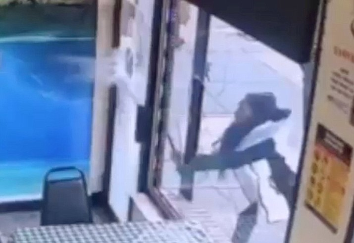 "In this surveillance video, a woman smashes the windows of ""Back Home Restaurant"" in the Bronx borough of New York. Police say that she became upset after ordering a beef patty and was told that the restaurant had run out of them. She returned with a bat and smashed two windows. (New York City Police Department via AP)"