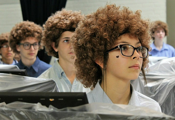 Madison Middle School art student Ariceli Martinez, wearing her Bob Ross wig, listens to the artist speak on a video screen before painting began on Flash Bob Flash Mob Day on Feb. 7, 2019 in Abilene, Texas The students donned their curliest wigs and painted little trees onto canvases to pay homage to the late painter Bob Ross. Teacher Brady Sloane said the idea came about because she wanted to reward Advanced Placement students who had been stressed out over recent projects and grades. (Greg Jaklewicz/The Abilene Reporter-News via AP)