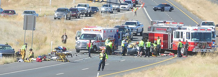 Lifeline Ambulance and Prescott Fire personel treat three victims of a two-vehicle collision near the Highway 89A and Granite Dells Parkway on-ramp in this Courier file photo. (Les Stukenberg/Courier)