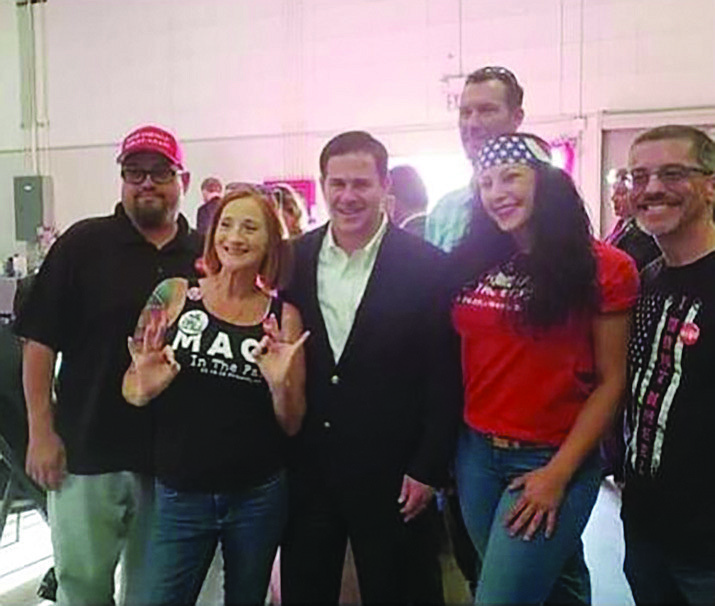 """Members of Patriot Movement AZ flashed what appeared to be a """"white power"""" sign when they posed with Gov. Doug Ducey for this photo in April at Mohave County Fairgrounds. (Courtesy file photo)"""