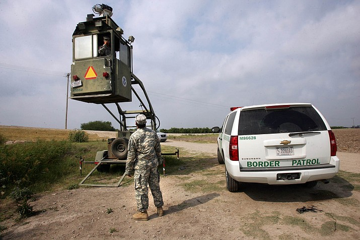 In this April 19, 2011, file photo, a member of the National Guard checks on his colleague inside a Border Patrol Skybox near the Hidalgo International Bridge in Hidalgo, Texas. National Guard members along the Texas-Mexico border assist Border Patrol by surveying the terrain from the tower. All major Republican presidential candidates have promised to secure the U.S.-Mexico border. Many support a fence stretching nearly 2,000 miles to do so. But a border that is sealed to all illegal immigrants and drugs is a promise none of them could keep. (Delcia Lopez/AP, File)
