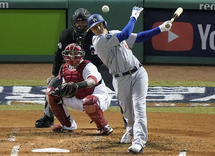 In this Oct. 24, 2018, file photo, Los Angeles Dodgers' Manny Machado, right, hits a single in front of Boston Red Sox catcher Christian Vazquez during the fourth inning in Game 2 of the World Series baseball game in Boston. (Elise Amendola/AP, file)