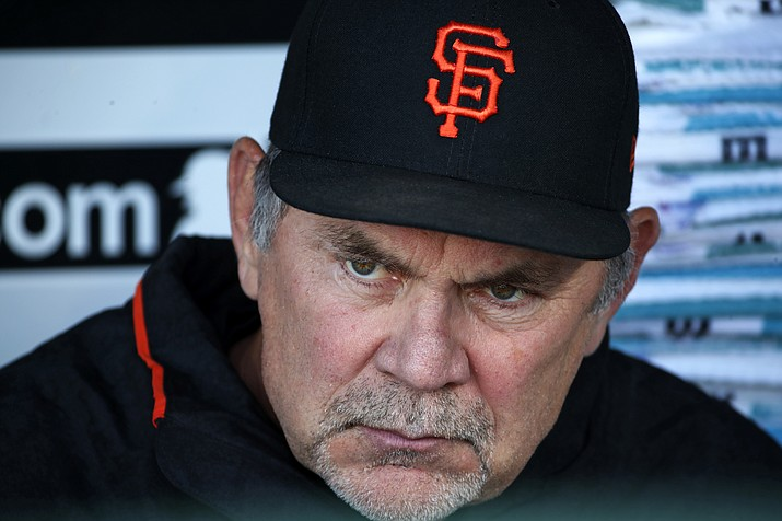 In this May 11, 2018 file photo, San Francisco Giants manager Bruce Bochy sits in the dugout before a baseball game against the Pittsburgh Pirates in Pittsburgh. The Giants have had a quiet offseason, aside of course from acquiring new president of baseball operations Farhan Zaidi from the rival and six-time defending division champion Dodgers and challenging him with getting this proud franchise back into contention.  (Gene J. Puskar/AP, file)