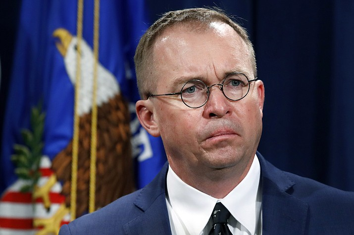 In this July 11, 2018, file photo Mick Mulvaney, acting director of the Consumer Financial Protection Bureau (CFPB), and Director of the Office of Management, listens during a news conference at the Department of Justice in Washington. White House Acting Chief of Staff Mick Mulvaney isn't setting any lofty goals for this weekend's meeting with a bipartisan mix of legislators at Camp David, but he is trying to build relationships across the aisle. (Jacquelyn Martin/AP, file)