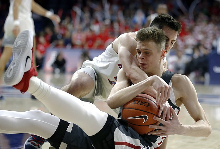 Arizona guard Alex Barcello and Washington State forward Aljaz Kunc, front, scramble for the ball during the second half of an NCAA college basketball game Saturday, Feb. 9, 2019, in Tucson, Ariz. Washington State won 69-55. (Rick Scuteri/AP)