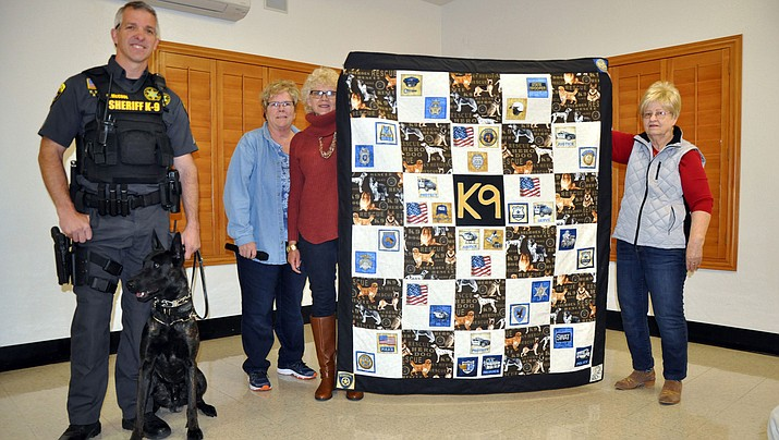Mohave County Sheriff Sgt. K. McCool and his K-9 partner, Chase, accept a homemade quilt last Thursday, Feb. 7 from the Red, White and Blue Quilters of Meadview members Rita Caldwell, Brenda Porzio and Marty Forsythe.