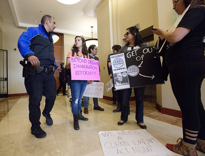 A small group of protesters are escorted out of the building housing Fla. Sen. Bill Nelson's office Jan. 18, 2018, in Coral Gables, Fla. A Koch brothers-funded group is sending young immigrants to lobby Congress to push for immigration reform and money for border security initiatives. (Wilfredo Lee/AP, file)