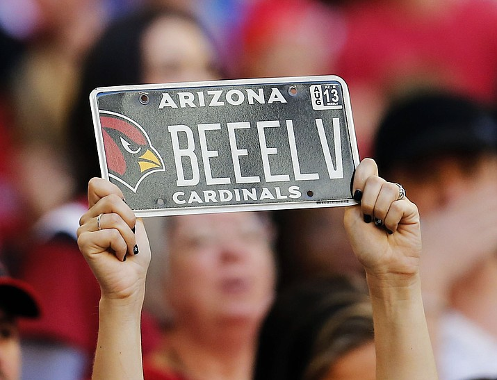 An Arizona Cardinals fan holds a license plate during the first half against the San Francisco 49ers on Dec. 29, 2013, in Glendale. On a 24-6 margin the Senate voted Monday to repeal a year-old $32-a-vehicle registration fee designed to fund the state Highway Patrol. The measure now goes to the House. (Matt York/AP, file)