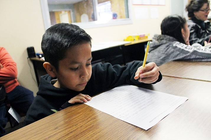 Corde Chiquito, a fourth grade student works on his Navajo language homework at the Pathways after school program Feb. 7 in Flagstaff. (Joshua Butler/NHO)