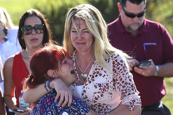 In this Feb. 14, 2018, file photo, Mechelle Boyle, right, embraces Cathi Rush as they wait for news after reports of a shooting at Marjory Stoneman Douglas High School in Parkland, Fla. The image become emblematic of the Parkland school massacre: two terrified moms outside the school, one of them a tall, weeping blonde with the black smudge of Ash Wednesday on her forehead, the other a petite redhead crying in despair on her shoulder. (AP Photo/Joel Auerbach, File)