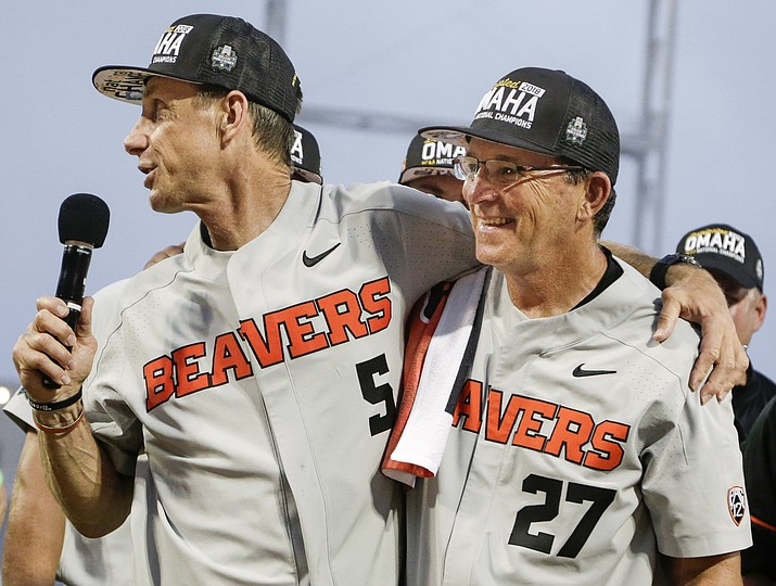 In this June 28, 2018, photo, former Oregon State coach Pat Casey, left, celebrates with his associate head coach Pat Bailey, after beating Arkansas for the NCAA College World Series baseball championship, in Omaha, Neb. Bailey, now Oregon State's interim head coach, is taking over the program that won the 2018 national championship and 111 of its last 130 baseball games. The 63-year-old was an assistant to former coach Pat Casey for 11 years. The Beavers bring back most of their pitchers but must replace six everyday position players. (Nati Harnik/AP, file)