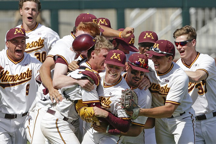 In this May 27, 2018, file photo, Minnesota players, including closing pitcher Max Meyer, bottom center, celebrate their 6-4 win over Purdue in the NCAA Big Ten baseball championship game in Omaha, Neb. The Gophers will be led again by Big Ten pitcher of the year Patrick Fredrickson and closer Max Meyer. (Nati Harni/AP, file)