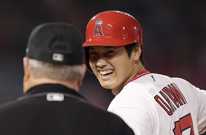Los Angeles Angels' Shohei Ohtani, right, of Japan, smiles at first base umpire Joe West after hitting a single during the second inning of a baseball game against the Oakland Athletics, Friday, Sept. 28, 2018, in Anaheim, Calif. (Mark J. Terrill/AP)