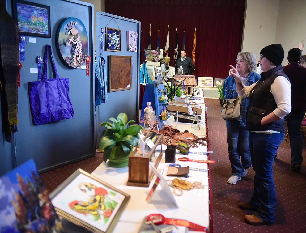 Carolynn and Kayla Wood look at some of the artwork on display at the Prescott VA Veteran's Creative Arts Festival Wednesday, Feb. 13, 2019. 128 pieces are on display at the 25th annual show being held in Building 15, theatre. (Les Stukenberg/Courier).