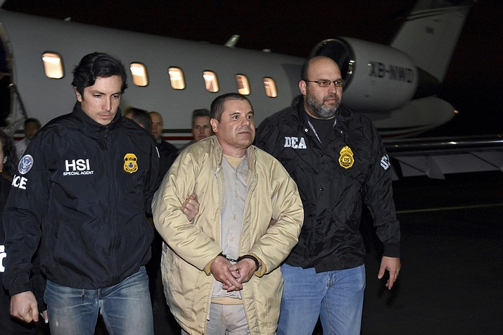 """In this Jan. 19, 2017 file photo provided U.S. law enforcement, authorities escort Joaquin """"El Chapo"""" Guzman, center, from a plane to a waiting caravan of SUVs at Long Island MacArthur Airport, in Ronkonkoma, N.Y. The Sinaloa cartel marches on following the conviction in New York of kingpin Joaquin """"El Chapo"""" Guzman on Tuesday, Feb. 12, 2019. (U.S. law enforcement via AP, File)"""