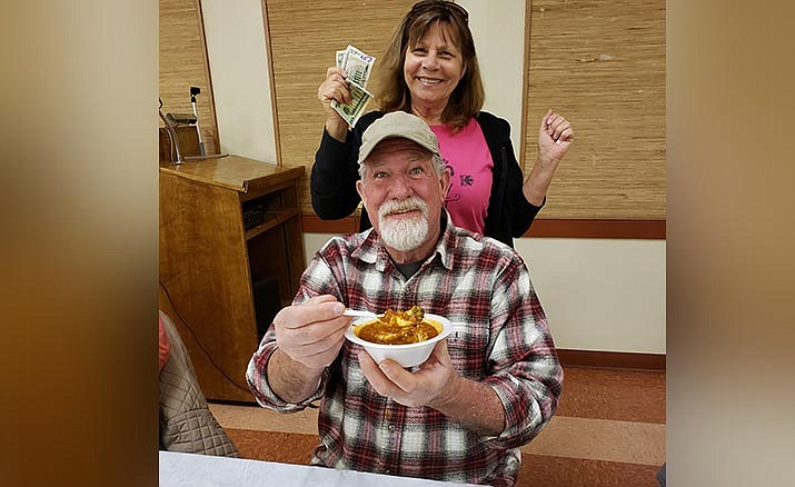 Chili Cook-off winner Belinda Milburn and her winnings with chili taster Chris Kinderman.