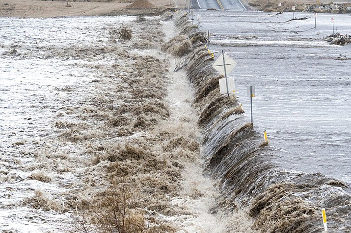 The Mojave River floods over Rock Springs road in Hesperia, Calif. on Thursday, Feb. 14, 2019. The road was closed due to flooding. (James Quigg/The Daily Press via AP)