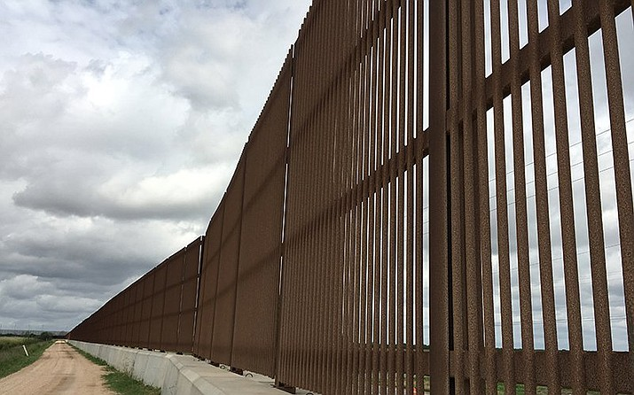 A border wall already runs up to both sides of the River Bend Resort & Golf Club in Brownsville, Texas. Erected in 2006, this part of the wall stands 18 feet and ends abruptly along a busy highway, leaving a gap several miles wide. Much of the most-recent border wall contruction has been in Texas and California. (Mindy Riesenberg, Cronkite News/Courtesy)