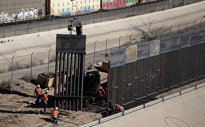 Workers place sections of metal wall Tuesday, Jan. 22, 2019, as a new barrier is built along the Texas-Mexico border near downtown El Paso. (Eric Gay/AP)