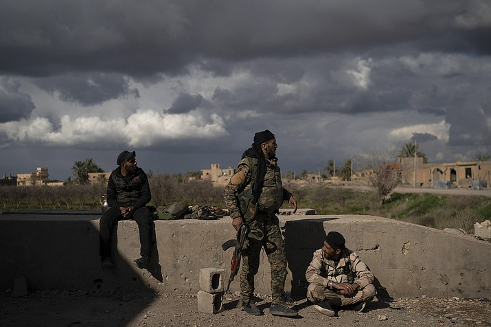 U.S.-backed Syrian Democratic Forces (SDF) fighters stand in an area recently taken by SDF as fight against Islamic State militants continue in the village of Baghouz, Syria, Sunday, Feb. 17, 2019.  (Felipe Dana/AP)