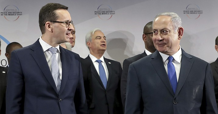 In this Thursday, Feb. 14, 2019 photo Poland's Prime Minister Mateusz Morawiecki, left, and Israeli Prime Minister Benjamin Netanyahu, right, attend a group photo during a meeting in Warsaw, Poland.  (AP Photo/Michael Sohn)
