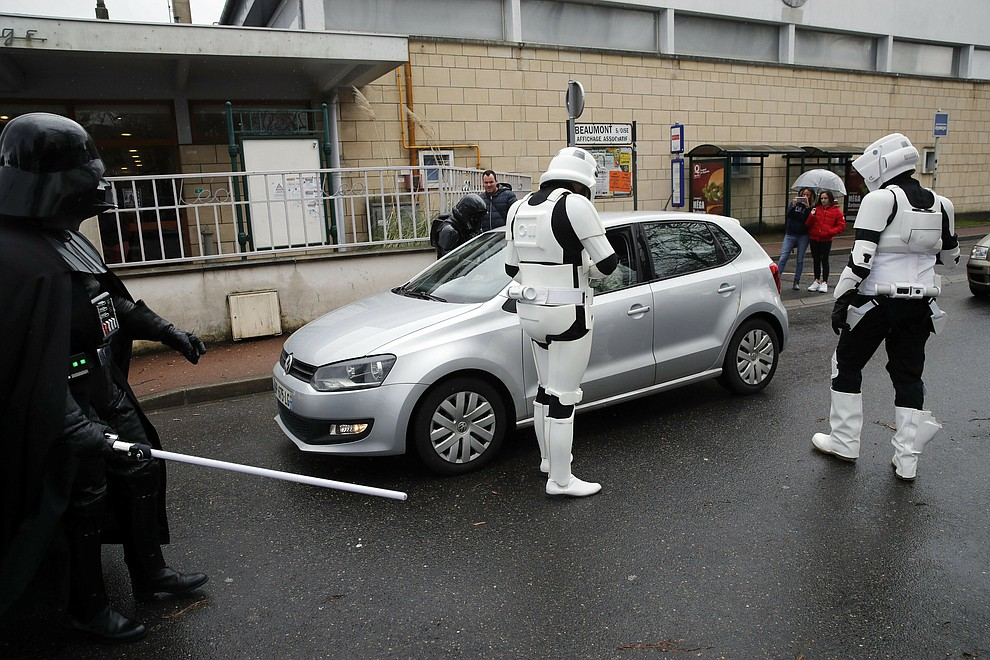 "In this Sunday, Feb. 10, 2019, photo, men dressed up as Stormtroopers joke as they approach a vehicle during a national lightsaber tournament in Beaumont-sur-Oise, north of Paris. In France, it is easier than ever now to act out ""Star Wars"" fantasies. The fencing federation has officially recognized lightsaber dueling as a competitive sport. (AP Photo/Christophe Ena)"