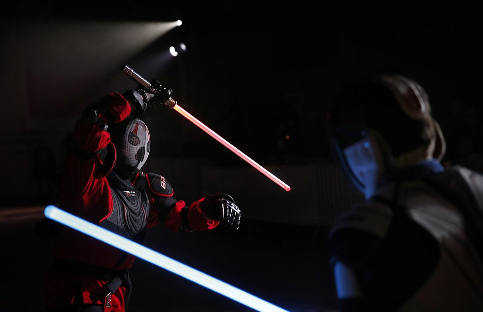 "In this Sunday, Feb. 10, 2019, photo, Julien Esprit, left, competes with Jean Baptiste Marchetti-Waternaux during a national lightsaber tournament in Beaumont-sur-Oise, north of Paris. In France, it is easier than ever now to act out ""Star Wars"" fantasies. The fencing federation has officially recognized lightsaber dueling as a competitive sport. (AP Photo/Christophe Ena)"