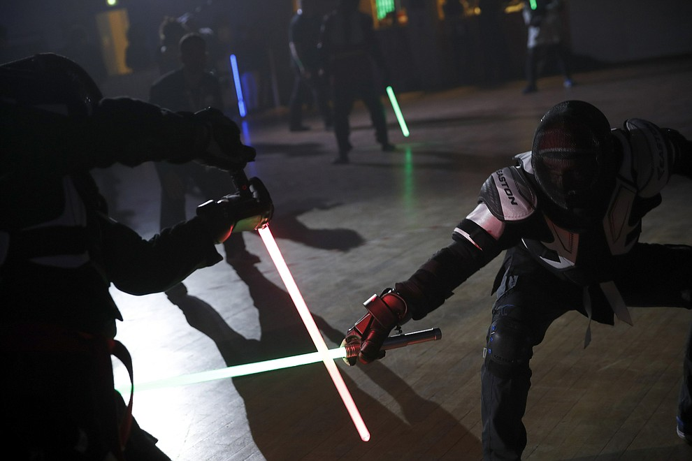 "In this Sunday, Feb. 10, 2019, photo, competitors battle during a national lightsaber tournament in Beaumont-sur-Oise, north of Paris. ""We wanted it to be safe, we wanted it to be umpired and, most of all, we wanted it to produce something visual that looks like the movies, because that is what people expect,"" said Michel Ortiz, the tournament organizer. (AP Photo/Christophe Ena)"